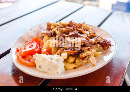 Delicious greek gyros with french fries, vegetables and tzatziki sauce on white plate - Stock Photo