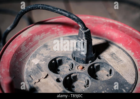 electric cable plugged into roll up extension cord with four european outlets or sockets - Stock Photo