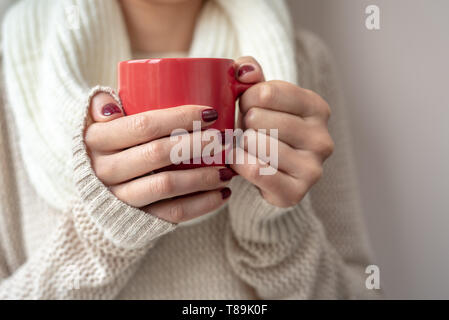 Young woman holds a cup with a hot drink in her hands. - Stock Photo