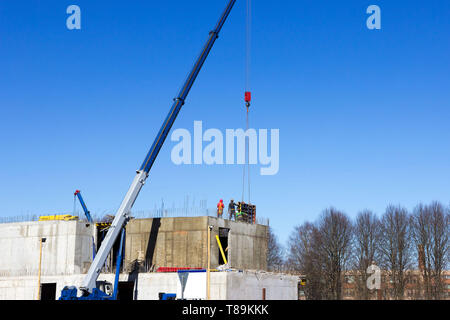 the worker and the crane operator unload the car with reinforced concrete walls for building a large wellness center with a swimming pool of modern - Stock Photo