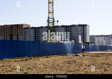 the worker and the crane operator unload the car with reinforced concrete walls for the future high-rise building. reportage shooting - Stock Photo