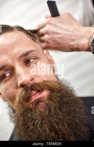 Stylish barber cuts a brutal man with a thick beard. - Stock Photo