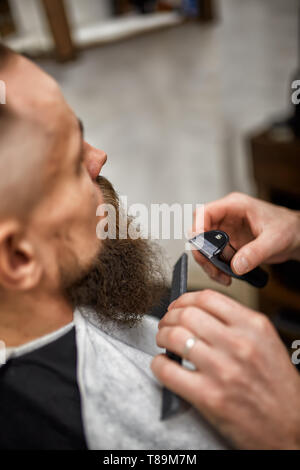 Side view of crop male face in hair salon trimming red beard and barber's hand holding hair clipper - Stock Photo