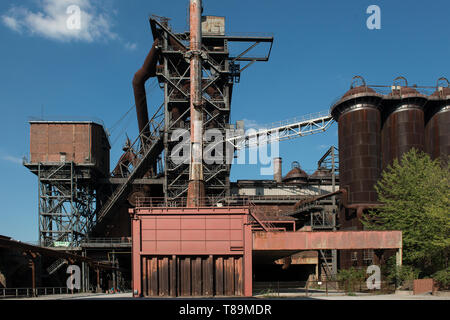 Landscape park in Duisburg with a closed down blast furnace factory on a sunny day with blue sky - Stock Photo