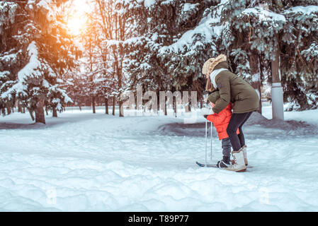 A young mother supports a young son, a boy of 3 years. In winter, outside in park, background is snow drifts of Christmas tree. Free space. Children's - Stock Photo