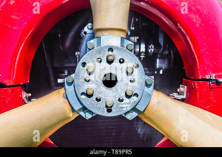 Close front view detail of vintage red biplane propeller, engine, mounting flange and bolts. - Stock Photo