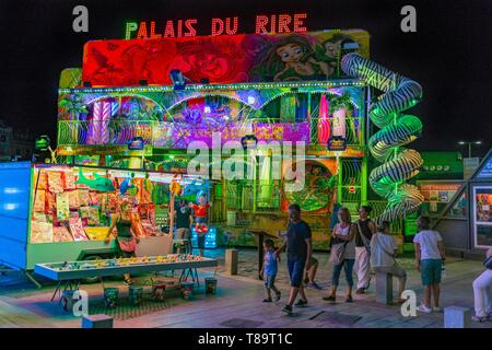 France, Herault, Sete, part) of Saint-Pierre, family passing in front ofa merry-go-round enlightened of night - Stock Photo