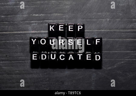Keep yourself educated on wooden blocks. Education, Motivation and inspiration concept - Stock Photo