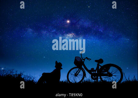 The person is cycling in the midst of the stars galaxy - Stock Photo