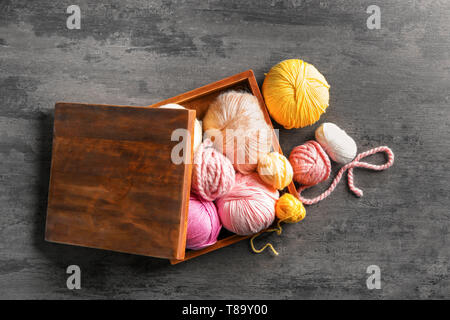 Wooden box with colorful knitting yarn on table - Stock Photo