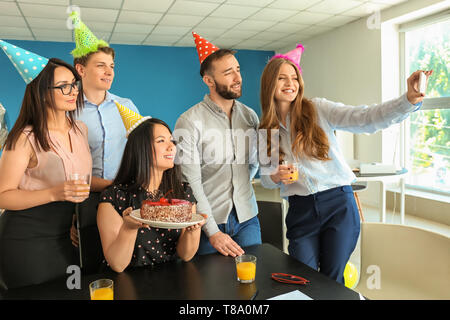 Young woman taking selfie with her colleagues at birthday party in office - Stock Photo
