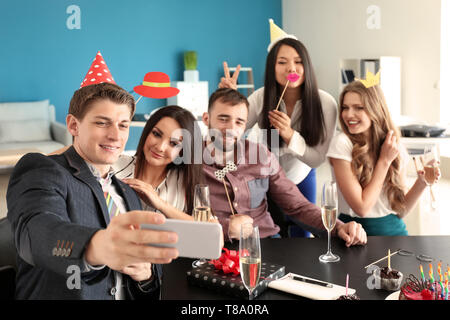 Young man taking selfie with his colleagues at birthday party in office - Stock Photo