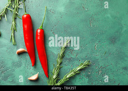 Fresh chili peppers with garlic and rosemary on color textured background - Stock Photo