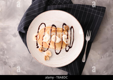 Plate with tasty pancakes, walnuts and sliced banana on table - Stock Photo