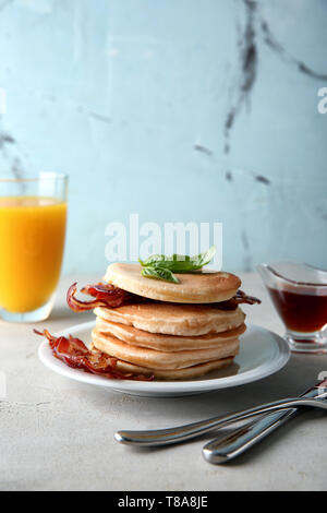 Tasty pancakes with fried bacon on table - Stock Photo
