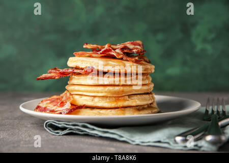 Tasty pancakes with fried bacon on plate - Stock Photo