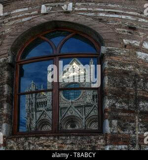 Santa Maria del Fiore; the cathedral of Florence reflected in neighbouring windows - Stock Photo