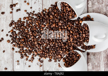 Black coffee in white cup and coffee beans on light wooden background. Top view, space for text - Stock Photo