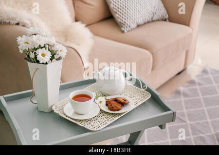 Table with teapot and chamomile flowers in interior of living room - Stock Photo