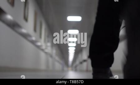 Man walks down the long white corridor. Blurred background. View from the back