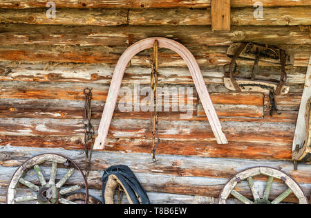 Vintage horse harnesses and wagon wheels next the barn wall in russian village - Stock Photo
