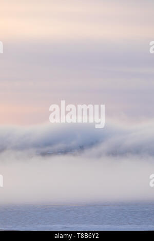 Thick fog at sunrise over hill and city buildings - Stock Photo