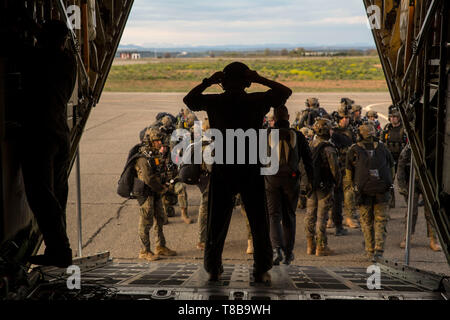 Multinational service members prepare to load onto a U.S. Marine Corps KC-130J Super Hercules with Special Purpose Marine Air-Ground Task Force-Crisis Response-Africa 19.2, Marine Forces Europe and Africa, during exercise Lone Paratrooper at Leon Air Base, Spain, May 6, 2019. SPMAGTF-CR-AF 19.2 supported the exercise with aerial-delivery Marines and a KC-130J Super Hercules. Lone Paratrooper is a multinational exercise hosted to improve training tactics, exchange knowledge, and increase relationships among allied and partner nations. SPMAGTF-CR-AF is deployed to conduct crisis-response and the - Stock Photo