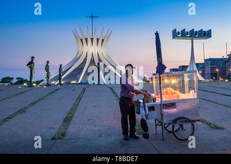 Brazil, Central-West, Federal District, Brasilia, Cathedral Our Lady of Aparecida designed by architect Oscar Niemeyer and classified World Heritage by UNESCO, street seller - Stock Photo