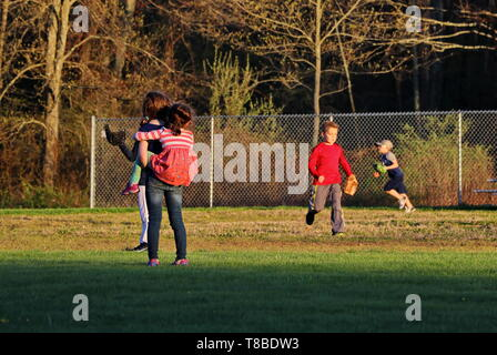 older sister gives youngest a piggy-back while they both look at boys playing baseball - Stock Photo