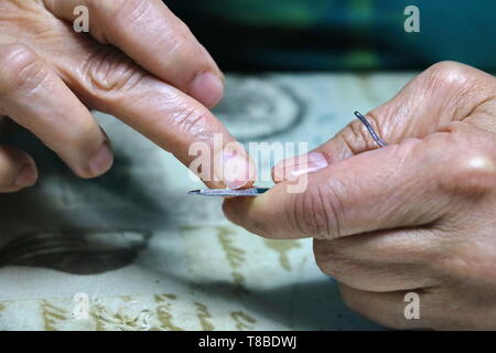 a woman filing and smoothing her recently cut nails - Stock Photo