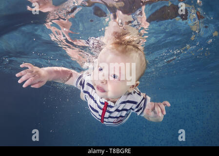 Little baby boy in a striped suit learns to swims underwater in the swimming pool. Healthy family lifestyle and children water sports activity. Child  - Stock Photo