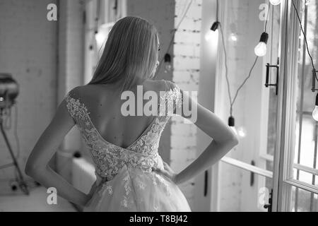 Graceful back of the bride. Looking out the window.Hairstyle - elegant bunch in the French style. - Stock Photo