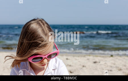 Funny little girl (7 years old) in sunglasses lies on the beach. Selective focus. - Stock Photo