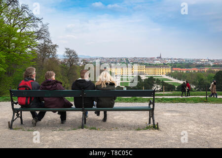Vienna palace, rear view of tourists sitting on a bench looking towards the  palace and gardens of Schloss Schönbrunn in Vienna, Wien, Austria. - Stock Photo