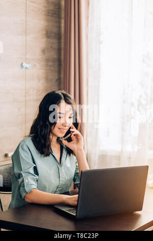Serious young caucasian female entrepreneur talking on cell phone and working on laptop while sitting at table in her home office. Freelancer, trainin - Stock Photo