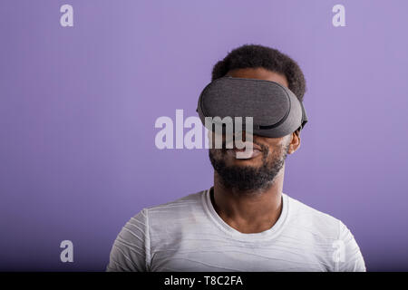 Young dark skinned man dressed in casual outfit wearing mobile virtual reality headset for playing 3D game isolated on purple background. VR technolog