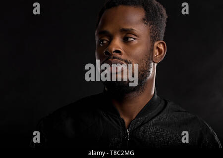 Highly detailed closeup portrait of attractive young african man wearing black jacket looking at camera with serious and thoughtful expression on dark - Stock Photo