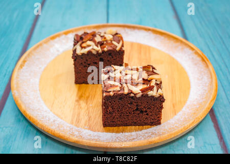 Homemade brownie cake decorated with almond and chocolate. - Stock Photo