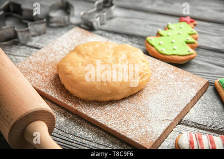 Raw dough for Christmas cookies on wooden board - Stock Photo