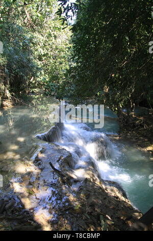 Scenic view on cascades and natural blue pool of idyllic Kuang Si waterfalls in jungle near Luang Prabang, Laos - Stock Photo