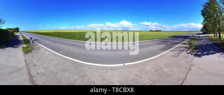 Stunning high resolution panorama of a northern german agricultural landscape on a sunny day with white cloud formations on a blue sky - Stock Photo