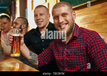 Happy male hipster with tattoo keeping glass of beer, looking at camera, smiling and posing in cafe. Young man drinking alcohol with friends, resting and enjoying evening. Concept of fun. - Stock Photo