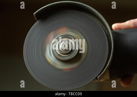 In the hand of a working grinding machine with a cutting wheel on a dark background. Power tool. The wheel rotates. - Stock Photo