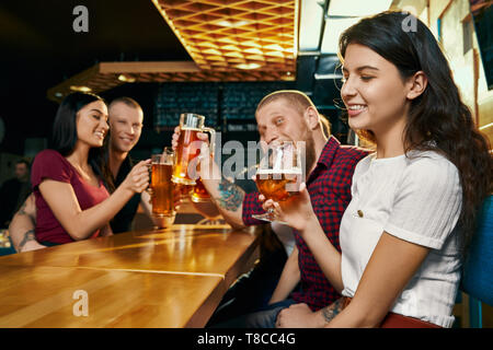 Side view of young smiling brunette enjoying free time with happy friends and drinking beer in bar. Cheerful company drinking alcohol, talking and laughing in pub. Concept of beverage and fun. - Stock Photo