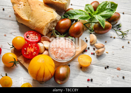 Composition with fresh cherry tomatoes and bread on white wooden background - Stock Photo