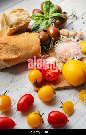 Fresh cherry tomatoes and bread on white wooden table - Stock Photo