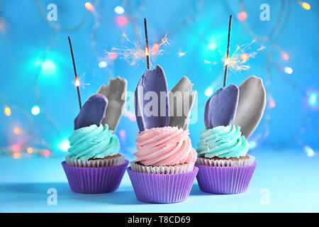Delicious birthday cupcakes with sparklers against blurred lights - Stock Photo