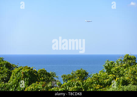 Stunning view of an airplane flying over a beautiful calm sea with blurred rich vegetation in the foreground. Phuket, Thailand. - Stock Photo