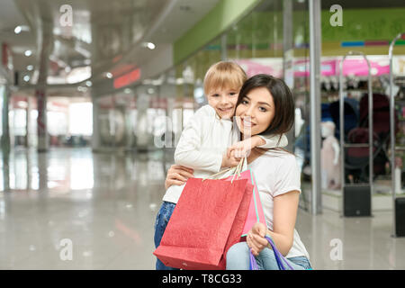 Cheerful woman and girl in big shopping center near shopwindow. Happy, cute, pretty child hugging young, beautiful mother, holding shopping paper bags and smiling. - Stock Photo