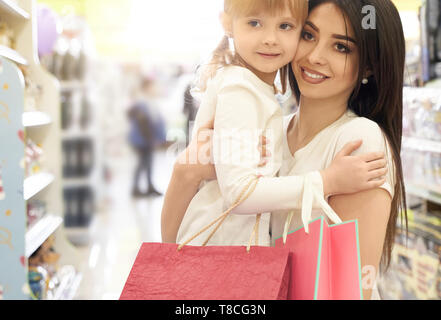Family shopping. Portrait of young mother and cute daughter in shopping center. Brunette holding on hands and hugging girl. Cheerful woman smiling. Child holding shopping paper bags. - Stock Photo